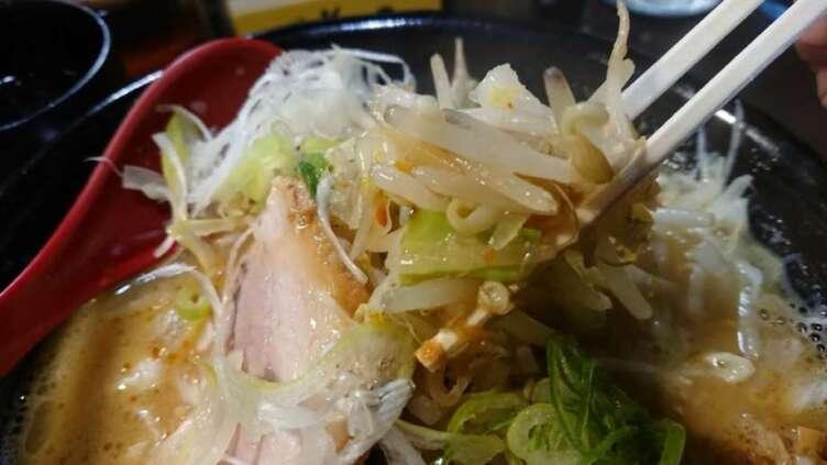 味噌ラーメンの上の野菜炒めを食べるところ
