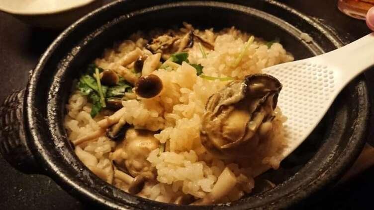 しゃもじで取り分ける牡蠣土鍋飯