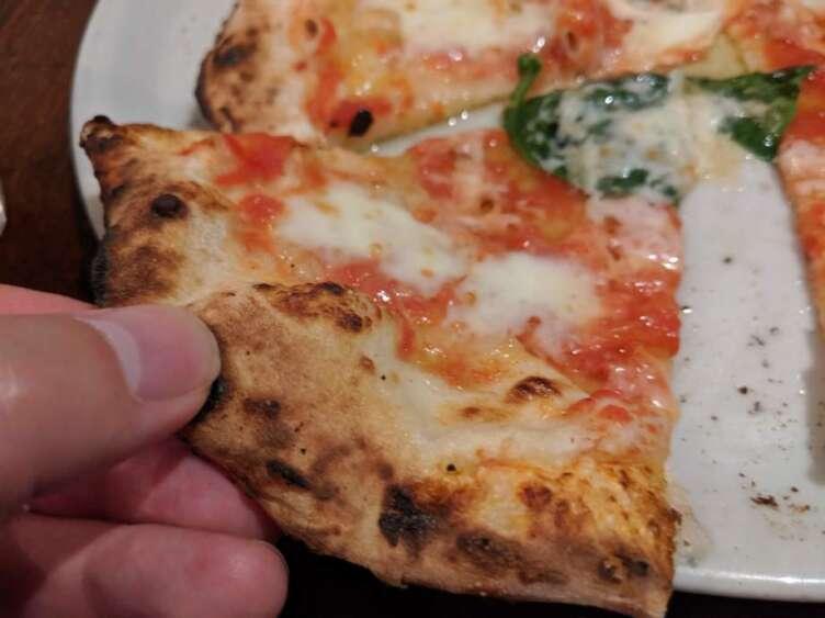 手でもったマルゲリータピザ