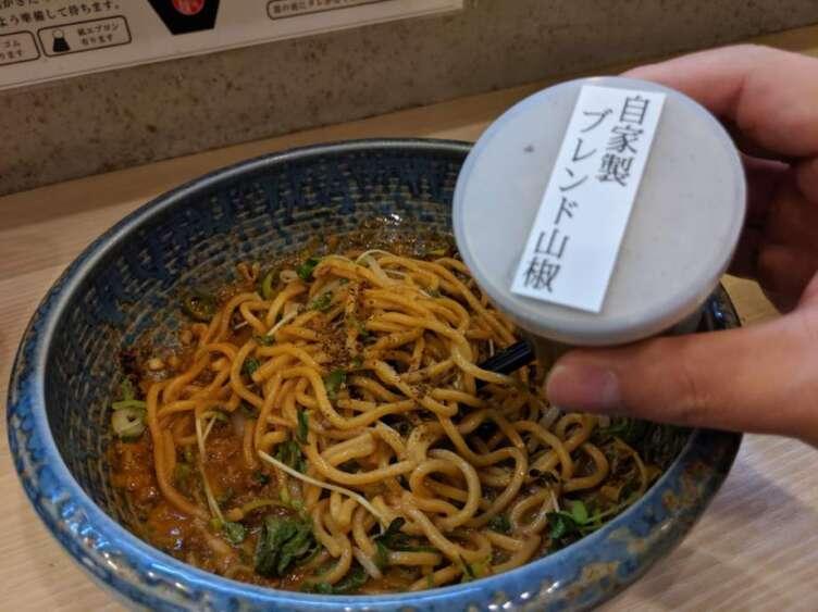 坦々麺に山椒をふりかけるところ